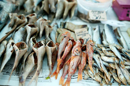 Dried fish on rope at stall on summer market for sale. Salted local seafood. Fishing concept. Stock Photo