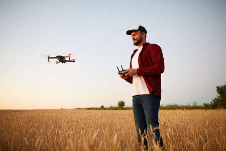 Farmer holds remote controller with his hands while quadcopter is flying on background. Drone hovers behind the agronomist in wheat field. Agricultural new technologies and innovations. Back view Stock Photo