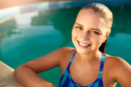 Portrait of attractive emotional blonde girl smiling in the pool side. Young teen wet woman with burning eyes came out of water and looking at camera. Happy tanned female in drops of water swimming. Imagens