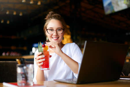 Smiling mixed race woman with cocktail in hand works with laptop. Businesswoman in glasses drinks juice for body hydration while working. Attractive designer quench thirst. Healthy lifestyle theme.