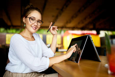 Digital artist finger touches convertible to 2 in 1 laptop display in tent mode and holds stylus. Mixed race multiethnic asian caucasian woman working on project design, writing notes on touchscreen.