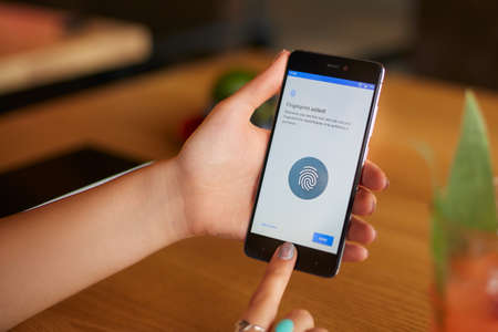 Female scanning fingerprint on her smartphone with program script on laptop display on backround. Woman unlock mobile phone with biometric sensor and finger. Privacy and security concept. Stock Photo