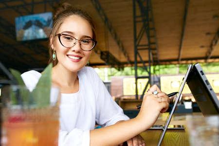 Freiberufliche gemischte Rassenfrauenhand, die mit Stift auf konvertierbarem Laptopbildschirm im Zeltmodus zeigt. Asiatisches kaukasisches Mädchen, das 2 in 1 Notizbuch mit Touchscreen zum Zeichnen und Arbeiten am Entwurfsprojekt verwendet.