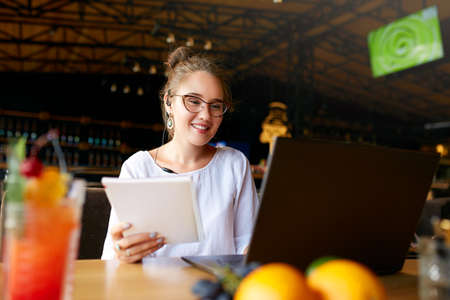 Businesswoman working remotely at cafe with headset and laptop. Mixed race female performing business negotiations on video chat. Telecommuting concept. Freelancer speaking on cellphone via headset.