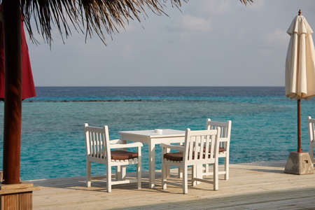 White empty table table and chairs at tropical resrraunt on open terrace in maldives. Blue ocean lagoon on background. No people. Stock Photo