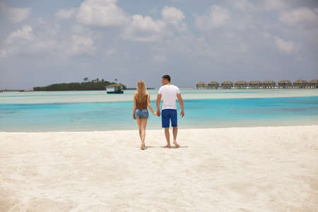 Back view of couple holding hands and walking to the blue ocean lagoon on Maldives at luxury spa resort. Travel and honeymoon concept.