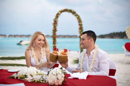 Groom and bride drink coconut cocktails at wedding table with lei of flowers on the beach of tropical island on Maldives. Turquoise ocean and ceremony arch on background. Stock Photo