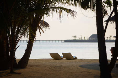 Beach chairs. Indian ocean coastline on Maldives island. White sandy beach and calm sea. Travel and vacation concept.