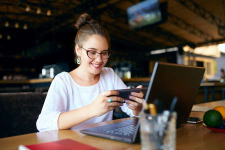 Mixed race business woman distracted from work on the laptop watching video on smartphone. Freelancer holding mobile phone and browsing using high speed 4g or 5g internet playing mobile games at work Stock Photo