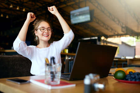Portrait of happy young business woman celebrating success with arms up in front of laptop. Mixed race female won a lot of money in lottery prize, raised arms with fists. Freelancer finished project. Stock Photo