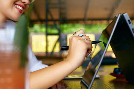 Isolated side view of freelancer woman hand pointing with stylus on convertible laptop screen in tent mode. Girl using 2 in 1 notebook with touchscreen for drawing and work on design project.