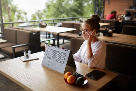 Mixed race freelancer working with convertible laptop using stylus and talking on cellphone with client in cafe. Asian caucasian businesswoman in glasses conducts negotiations via phone call. Multitasking business concept. Stock Photo