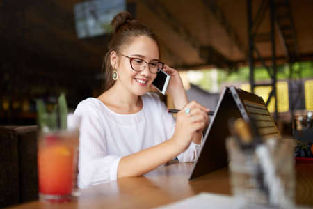 Mixed race freelancer working with convertible laptop and talking on cellphone with client in cafe. Asian caucasian businesswoman conducts negotiations via phone call. Multitasking business concept.
