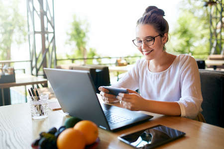 Handsome businessman distracted from work on the laptop watching video on smartphone. Freelancer holding mobile phone and browsing using high speed 4g or 5g internet. Man playing mobile games at work Stock Photo