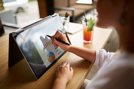 Businesswoman hand pointing with stylus on the chart over convertible laptop screen in tent mode. Woman using 2 in 1 notebook with touchscreen for work on business presentation. Isolated close view.