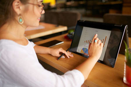 Businesswoman finger touching the chart over convertible laptop screen in tent mode. Freelancer woman using 2 in 1 notebook with touchscreen for work on business presentation. Isolated close view.