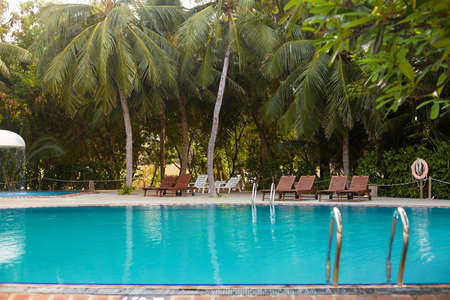 Swimming pool side of luxury hotel ith deck chairs, palm trees and blue ocean. Maldives