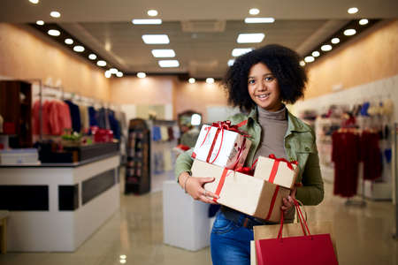 African american girl shopping gifts in mall on christmas sale. New year holidays concept. Smiling attractive mixed racial woman with colorful paper gift boxes wearing christmas hat in store or shop.