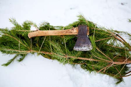 Axe on cut down spruce or pine christmas tree branches on snowy ground. Deforestation ban. Irresponsible behavior towards nature, keep green, save forest concept.