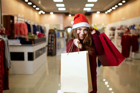 Happy girl shopping gifts in mall on christmas sale. New year holidays shopping idea concept. Smiling pretty caucasian woman with colorful paper presents bags wearing christmas hat in store or shop.