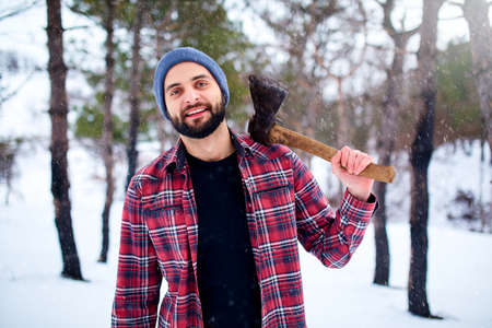 Bearded hipster man in a winter snowy forest with axe on a shoulder. Woodman standing in the forest. Male inspecting trees in woods. Lumberjack woodcutter holding ax wearing plaid red shirt. Archivio Fotografico