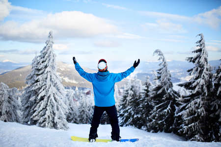 Snowboarder raised his arms and hands to the sky at ski resort. Man climbed a mountain top through forest for backcountry freeride enjoying beautiful landscape. Moment of rapture, freedom and glory. Stock Photo
