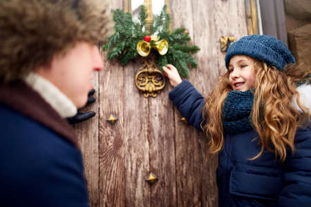 Little girl helps father and hanging Christmas wreath on the door. Cute curly daughter spend time with parents on holidays. New Year home decorations and preparations. Snowy winter outdoors.
