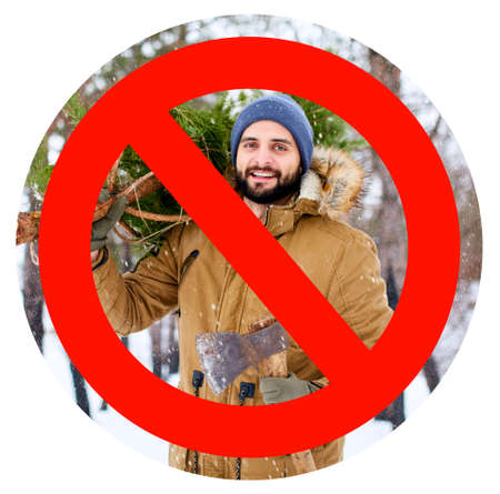 Crossed out red sign on bearded lumberjack man carrying freshly cut down christmas fir tree and axe in woods. Deforestation ban. Irresponsible behavior towards nature, save forest, keep green concept. Stock Photo