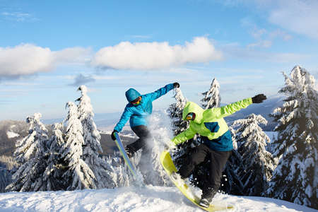 Two snowboarders doing tricks at ski resort. Riders friends performing jump with their snowboards near forest on backcountry freeride session in colorful fashionable outfit. Copyspace area. Stok Fotoğraf