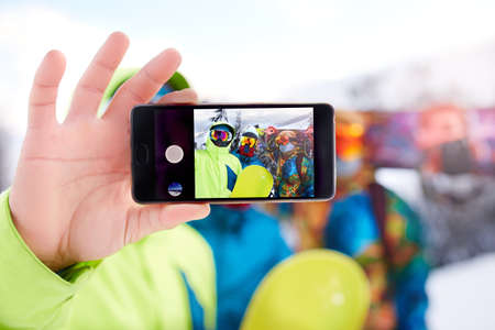 Smartphone screen with three snowboarders taking selfie at ski resort. Friends photographing for social network sharing with snowboards near forest wearing reflective goggles, colorful fashion clothes