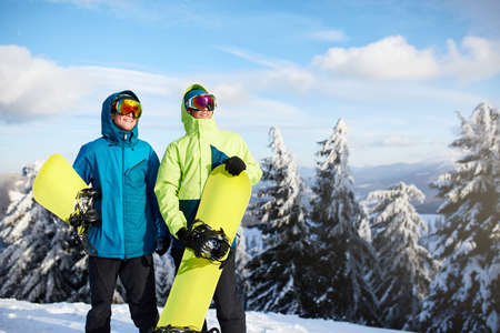 Two snowboarders posing at ski resort. Riders friends carrying their snowboards through forest for backcountry freeride and wearing reflective goggles, colorful fashion outfit. Copyspace area. Stockfoto