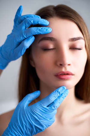 Beautician doctors hands in gloves touching face of attractive woman. Fashion blonde model after cosmetic treatment. Aesthetic cosmetology, plastic surgery concept. Modern female beauty standard. Фото со стока