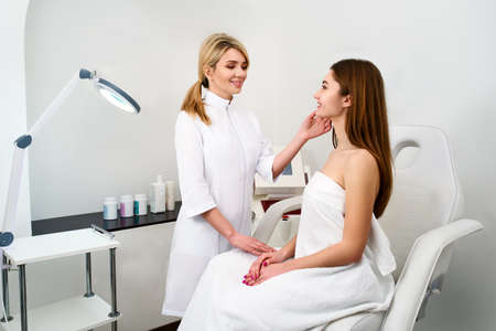 Plastic Surgeon or Cosmetology Specialist Examines Womans Face, Touches with Hands, Inspecting Healed Skin after Surgery with Amazing Results. Client Sitting on Checkup at Attending Physician Doctor.