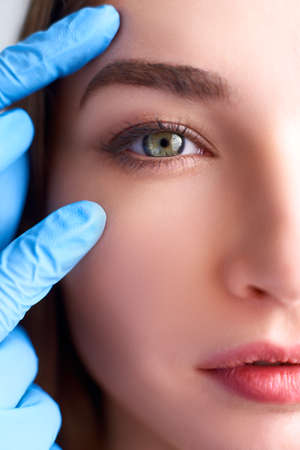 Upper eyelid reduction, double eye lid removal plastic surgery concept. Beautician doctor hands in gloves touching female face skin. Ophthalmologist or oculist checks healthy vision in green eyesight.