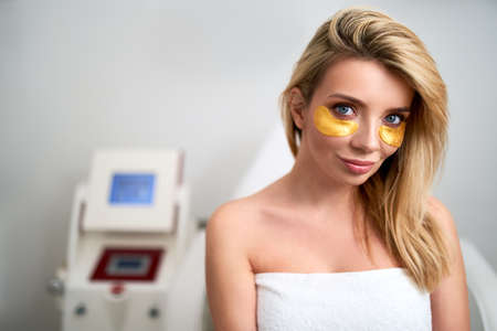Portrait of attractive blonde caucasian woman with golden eye patches showing an effect of perfect clean fresh skin after cosmetic procedures in beauty parlor. Female face in cosmetology room.