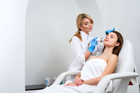 Pretty blonde beautician doctor doing rf-lifting procedure for woman laying in a beauty salon. Hardware cosmetology. Patient receiving electric facial massage. Skin rejuvenation and wrinkle smoothing.