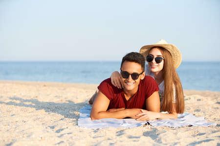 Feliz pareja interracial recién casados se encuentran al sol en un lugar de viaje tropical. Novio y novia se relajan en el balneario tomando el sol cerca de la laguna azul. Hombre joven y mujer con sombrero de paja en luna de miel.