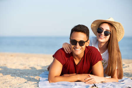 Happy interracial couple newlyweds lie in the sun on tropical travel location. Boyfriend and girlfriend relax at spa resort sunbathing near lagoon. Woman with teeth braces wearing straw hat.