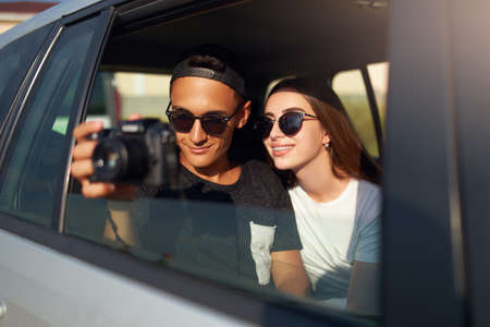 Blogger in glasses filming his travel vlog on professional camera on road trip. Man photographer taking photos out of open window with girlfriend nearby. Multiracial hipsters couple on rear car seat. Stock Photo