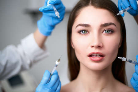 Hands of beauticians holding syringes around doll like woman face ready for injection in cosmetology clinic. Female model under influence of cosmetic treatment industry standardized beauty concept. Banco de Imagens