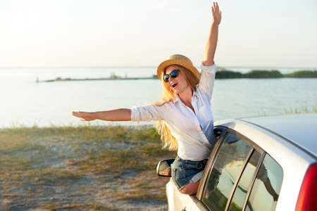Pretty woman in straw hat enjoying road trip on a summer holidays. Excited young female raising her hands of the car window. Girl riding sitting on car door and leaning out of window arrived at beach.