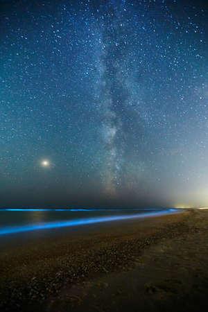 Photo longue exposition de plancton rougeoyant sur les vagues de la mer et la voie lactée. Lueur bioluminescente bleue de l'eau sous le ciel étoilé. Phénomène naturel arrière. Planète Mars lumineuse parmi les constellations dans le ciel nocturne.