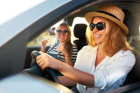 Twee jonge vrolijke glimlachende vrouwen in een auto op vakantiereis naar het zeestrand. Meisje in glazen besturen van een voertuig van verhuur op vakantie. Vriendinnen die van de zomer genoten, kwamen op vakantie naar de kust van de oceaan.