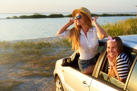 Two women enjoying road trip on a summer day at seaside. Excited young female friends leaning out of car windows and looking at beach and sea. Girl in sitting on car door and touching her straw hat. Stock Photo