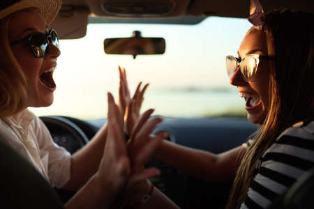 Happy excited young women driving in car and making high five gesture on summer vacation trip. Two girls rejoice they arrived at destination beach. Holidays near the sea or ocean. Summer lifestyle.