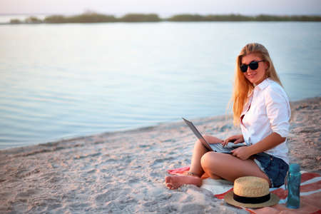 Authentic woman working with laptop on sea shore. Freelancer girl telecommuting with team on project on tropical island. Female using internet from computer while sitting on beach towel on sunset.