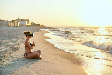 Woman in VR glasses doing yoga padmasana on ocean beach in the morning. Girl using virtual reality for deep immersion to feel herself at the seaside concept. Yoga online internet lessons with coach.