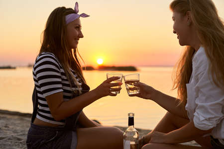 Women clink glasses with white wine on the beach. Girlfriends cheerfully celebrate vacation and proclaim toast on tropical island. Romantic picnic with alcoholic drink beverage near sea on sunset. Stock Photo