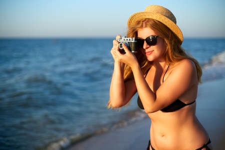 Young authentic woman with vintage retro film camera enjoying tropical beach on summer vacation. Female travel photographer in straw hat and bikini swimsuit taking photos having fun at the seaside.