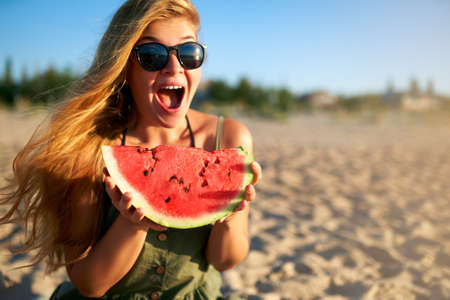 Happy young woman in glasses eating watermelon on the sandy beach on vacation. Girl joyfully holding fresh watermelon skip in her hands and have fun with hair fluttering in the wind. Youth lifestyle.